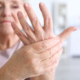 An elderly woman with arthritis grimacing while holding and massaging her left hand with her right hand.
