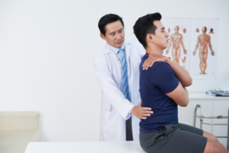 A male asian doctor examins a male asian patient's lower back as the patient sits up straight on an exam table.