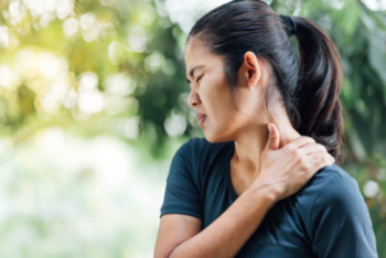 Young asian woman touching her neck while wincing in pain.